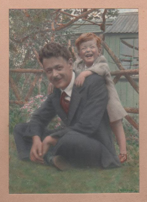 coloured photo of Father and me, he sitting crosss-legged on the grass, me standing leaning on his back, my arms on his shoulders and laughing.